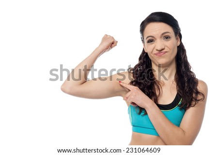Young fitness woman worries about her biceps