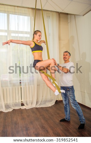 Young flexible attractive gymnast girl and her trainer posing in the gym - stock photo
