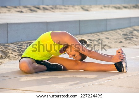 Young, flexible woman, stretching her legs on a sunny summer evening, touching her knee with her head during the warming up on a training and jogging run - stock photo