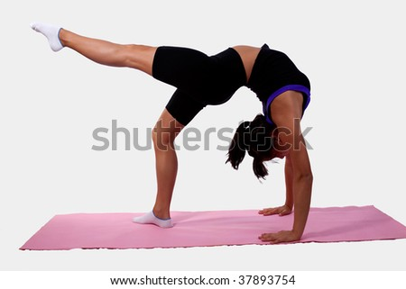 Young flexible woman wearing workout attire bending backwards while pointing foot standing on pink yoga mat