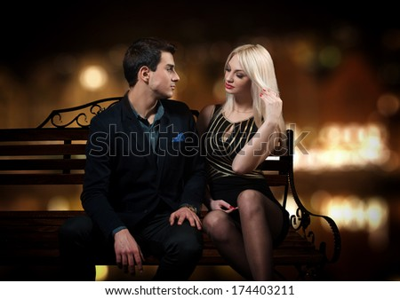 Young flirting couple sitting on a bench, night city background - stock photo