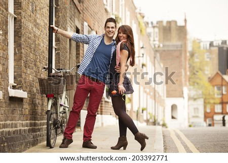 young flirty couple posing on street of Chelsea in Central London - stock photo
