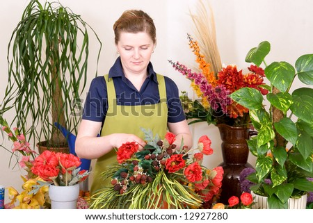 Young florist  working on an arrangement - stock photo