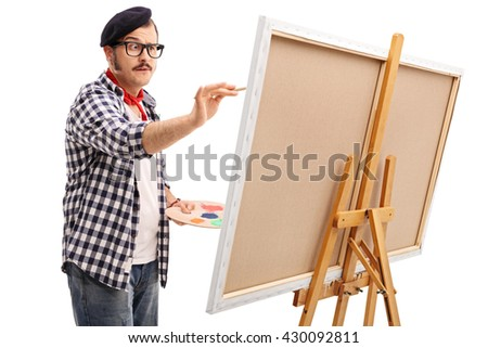 Young focused artist painting on a canvas isolated on white background - stock photo