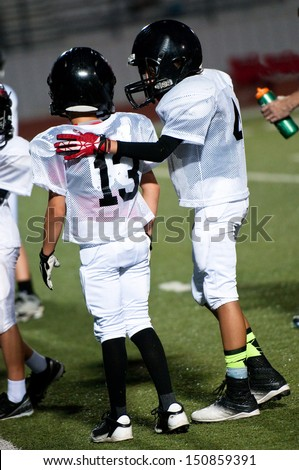 Young football boy putting his arm around his teamate. - stock photo
