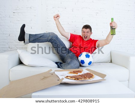 young football fan man watching game on television wearing team jersey celebrating goal crazy happy jumping excited on sofa couch at home with ball drinking beer bottle and eating pizza  - stock photo