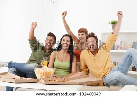 Young football fans sitting at home on sofa jittering, shouting. - stock photo