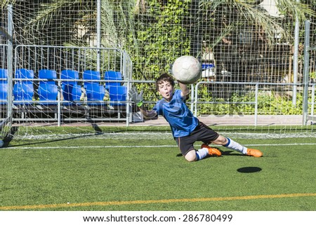 Young football goalkeeper stretching to stop a ball - stock photo