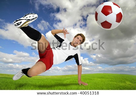 Young football player in a acrobatic pose kicking a ball in a green field - stock photo