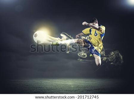 Young football player on stadium kicking ball - stock photo