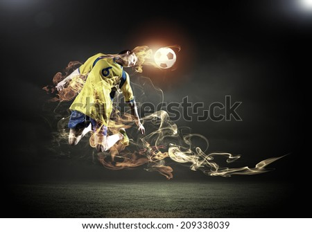 Young football player on stadium kicking ball with head in jump - stock photo