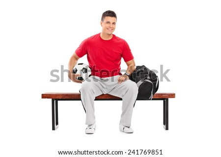 Young football player sitting on a bench isolated on white background - stock photo