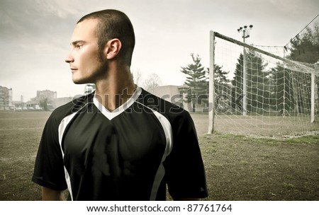 Young football player with football court in the background - stock photo