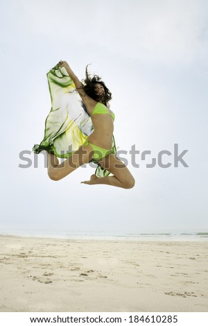 young football supporter jumping with Brazil flag on beach