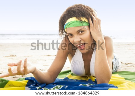 young football supporter on beach in team colors with Brazil flag  - stock photo