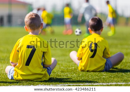 Young football team wearing sports yellow soccer dress. Soccer players on sports field. Football soccer match for children. Youth sports team sitting together and watching football soccer game. - stock photo