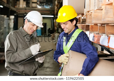 Young foreman looking at supervisor writing notes in warehouse - stock photo