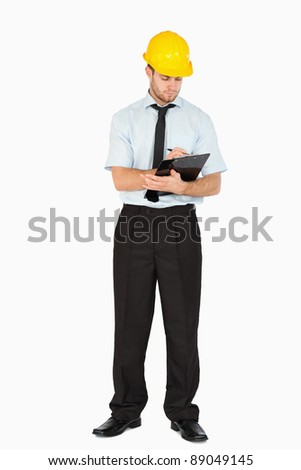 Young foreman taking notes on his clipboard against a white background