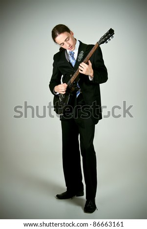 Young formal man playing on guitar - stock photo