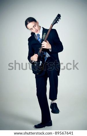 Young formal man rocking out with guitar - stock photo