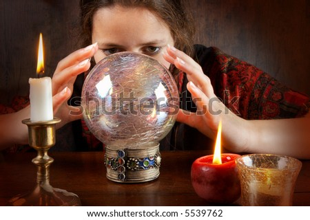 Young fortune teller in a red scarf working with her crystal ball - stock photo