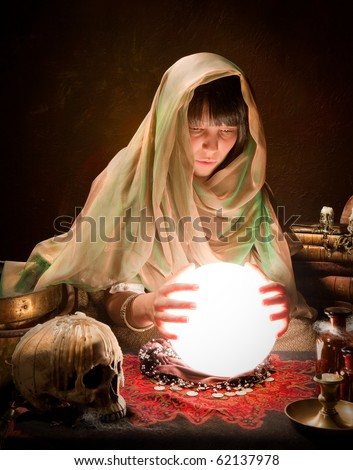 Young fortune-teller reading the future in a crystal ball - stock photo