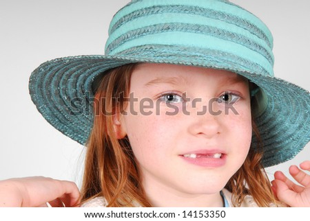 Young freckle faced girl in green hat