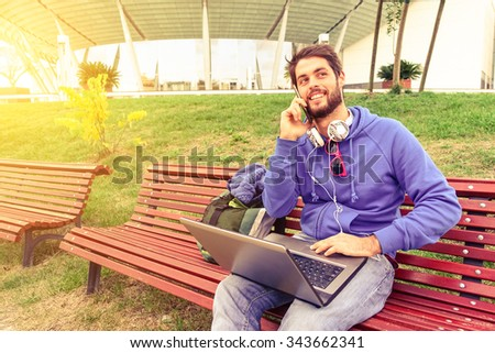 Young freelance man using mobile phone and laptop pc - Teenager student talking on smartphone in urban park - Smiling guy with wireless computer outdoor - Technology concept soft vintage marsala look - stock photo