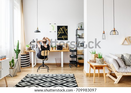 Young Freelance Woman Working Remotely At Designer Home In Cozy White  Office Room With Pendant Lamps