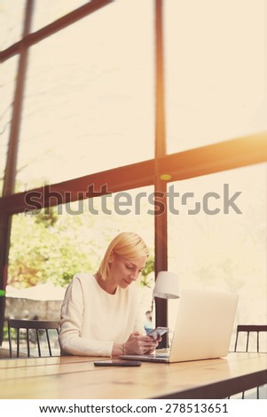 Young freelancer use smart phone sitting in modern loft interior with big windows, business woman text message at office desk,female student sitting at wooden table of modern university library,filter - stock photo