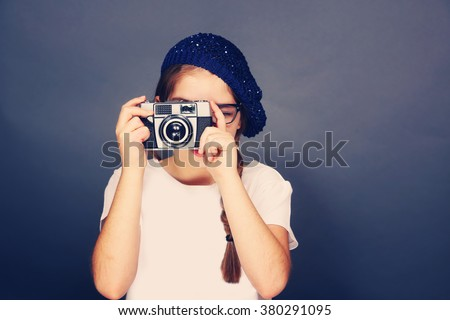 Young french girl taking a picture with a vintage film camera. Young fashion, photography, travel, foreign language learning and life style concept - stock photo