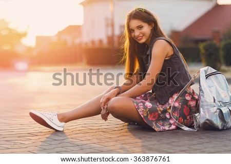 Young fresh cheerful hipster  girl  sitting on the road in countryside wearing stylish summer clothes, bright print skirt , neon  bag pack. Warm evening colors. Sunset. Lifestyle image. - stock photo