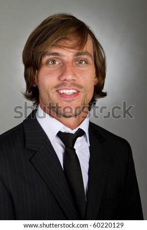 Young fresh confident businessman with longer hair over a greyish background. - stock photo