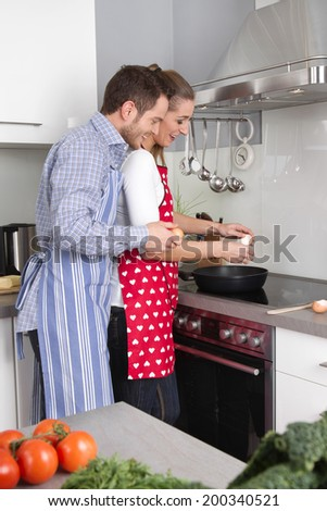 Young fresh married couple in the kitchen cooking together fried eggs.