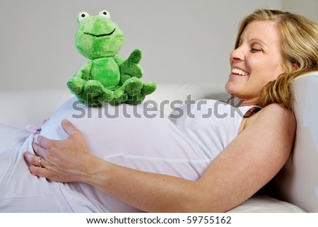 Young fresh pregnant woman with baby toys. Isolated over white background. - stock photo