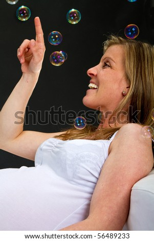 Young fresh pregnant woman with blow bubbles  sitting on a couch over black background. - stock photo