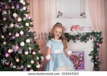 Young friendly girl stay near gift box and dressed Christmas tree. New Year celebration. - stock photo