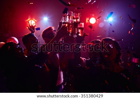 Young friendly people toasting in night club - stock photo