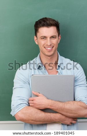 Young friendly university student holding a file while standing in front of a clean green blackboard in the classroom smiling at the camera