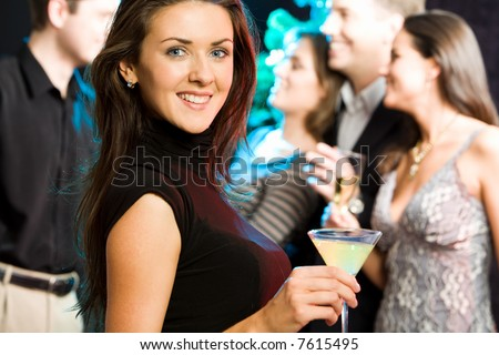 Young friendly woman looking at camera while a party - stock photo
