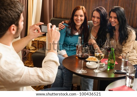 Young friends at the bar man take picture of three women - stock photo