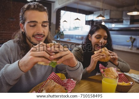 Young friends eating burgers at table in cafe