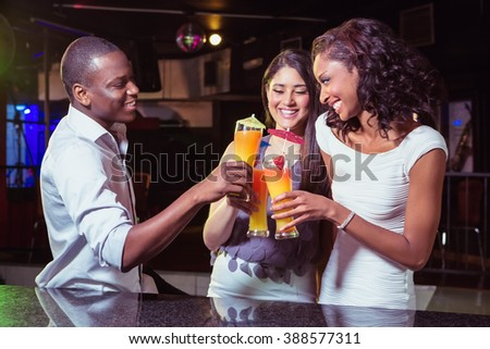 Young friends enjoying while having cocktail drinks at bar counter in bar - stock photo