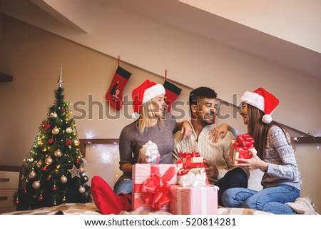 Christmas gift exchange stock images royalty free images young friends exchanging christmas gifts negle Choice Image