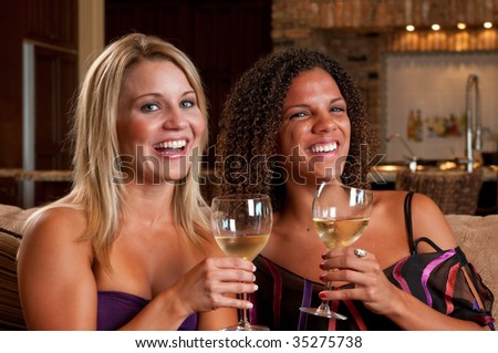 Young friends hanging out and drinking wine in a living room.