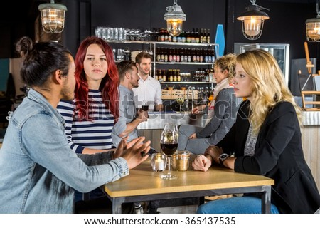 Young friends having conversation at table in bar