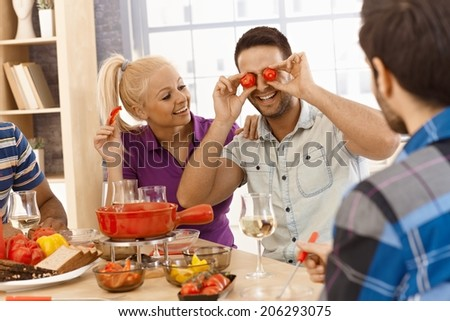 Young friends having fondue party, a man making eyes from tomatoes, laughing. - stock photo