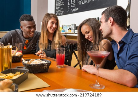Young friends having fun in a bar drinking cocktail.  - stock photo