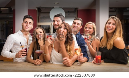 Young friends having fun in a bar drinking cocktail while watching TV. - stock photo