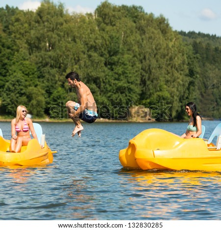 Young friends having fun jumping into water from pedal boats - stock photo
